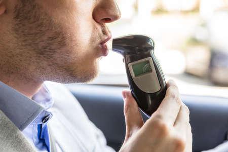 Photo pour Close-up Of A Young Man Sitting Inside Car Taking Alcohol Test - image libre de droit