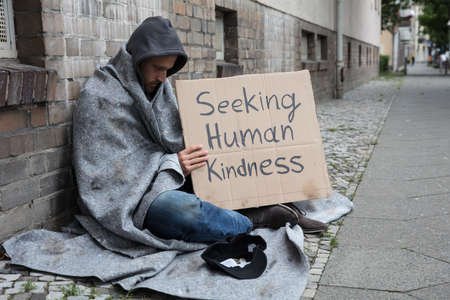 Photo for Male Beggar In Hood Showing Seeking Human Kindness Sign On Cardboard - Royalty Free Image