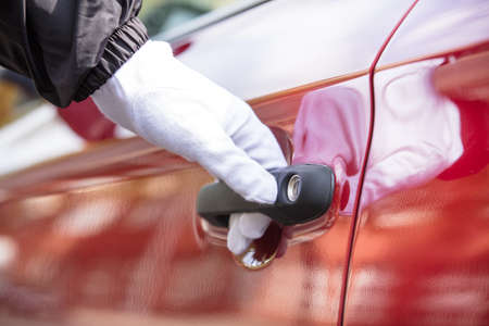 Photo pour Close-up Of A Valet's Hand Opening Red Car Doors - image libre de droit