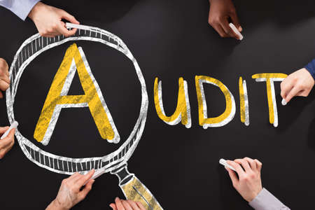 Foto de People Drawing Audit And Fraud Investigation Concept On Blackboard - Imagen libre de derechos