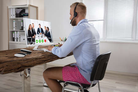 Foto de Businessman Dressed In Shirt And Shorts Having Video Call On Computer In The Home Office - Imagen libre de derechos