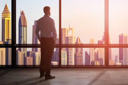 Foto de Businessman Standing At The Large Window Of A High Office Overlooking The Cityscape - Imagen libre de derechos