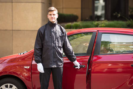 Photo pour Portrait Of A Happy Young Male Valet Opening Red Car Door - image libre de droit