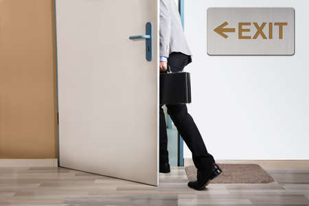Photo for Businessperson Walking Out With Exit Sign On Wall - Royalty Free Image