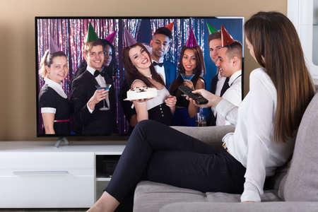 Foto de Woman Sitting On Sofa And Watching Television At Home - Imagen libre de derechos