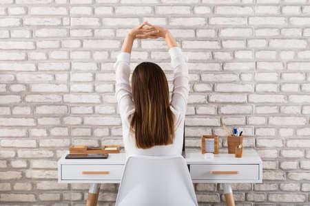 Foto de Rear View Of A Young Businesswoman Sitting On Chair Stretching Her Arms - Imagen libre de derechos