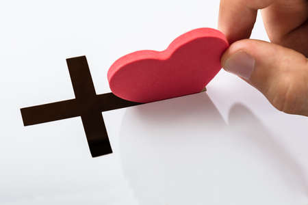 Foto de Hand Inserting Heart Shape In Crucifix Slot On White Background - Imagen libre de derechos