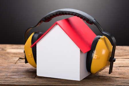 Photo pour Closeup of model home with ear protectors on wooden table against black background - image libre de droit