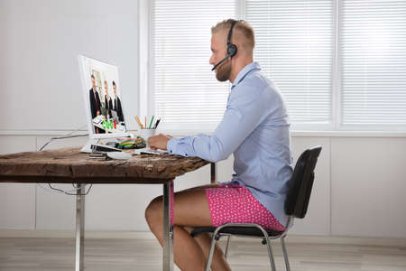 Photo pour Businessman Dressed In Shirt And Shorts Having Video Call On Computer In The Home Office - image libre de droit