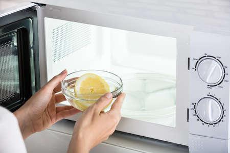 Photo pour Close-up Of Woman Putting Bowl Of Slice Lemon In Microwave Oven - image libre de droit