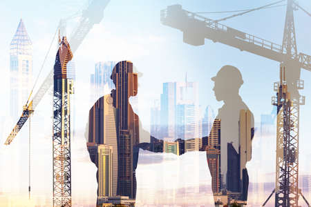 Foto de Double exposure of silhouette architects shaking hands over cranes and buildings background - Imagen libre de derechos