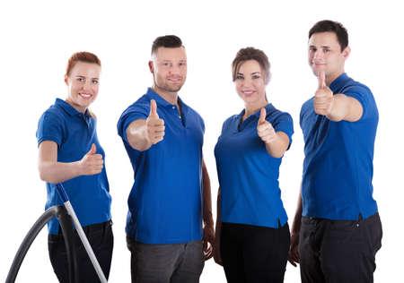 Foto de Portrait Of Happy Janitors Showing Thumb Up Sign Against White Background - Imagen libre de derechos