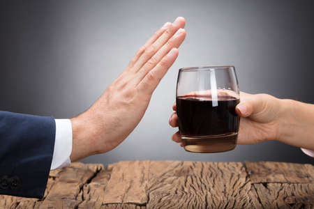 Photo for Businessperson Rejecting Glass Of Whiskey Offered By Colleague - Royalty Free Image