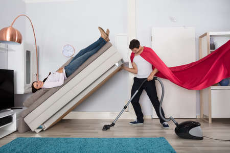 Foto de Young Man Wearing Red Cape Cleaning Under The Couch With Vacuum Cleaner - Imagen libre de derechos
