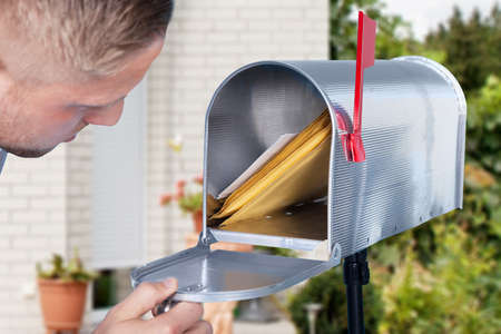 Foto de Close-up Of A Man Looking Inside The Silver Mailbox - Imagen libre de derechos