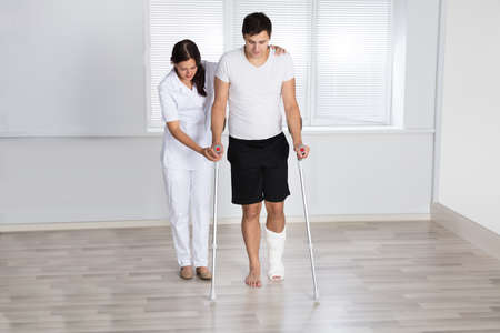 Photo pour Physiotherapist Assisting Injured Young Male Patient To Walk With Crutches In Clinic - image libre de droit