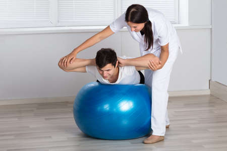 Photo pour Young Female Physiotherapist Assisting Man While Doing Exercise On Fitness Ball - image libre de droit