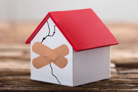Photo pour Broken House Model With Crossed marking On Wooden background - image libre de droit