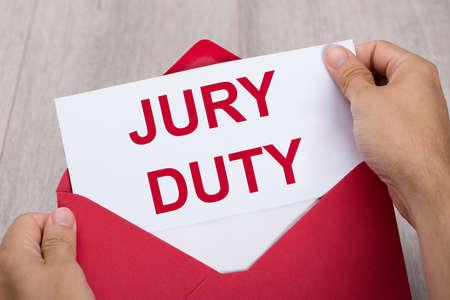 Foto de Close-up Of A Human Hand Holding Jury Duty Document In Red Envelope - Imagen libre de derechos