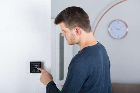 Foto de Young Man Adjusting Room Temperature On A Digital Thermostat At Home - Imagen libre de derechos