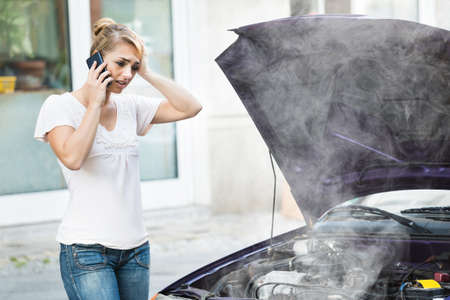 Foto de Young Woman Talking On Mobile Phone In Front Of Smokey Car Engine - Imagen libre de derechos