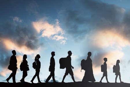 Foto de Silhouette Of Refugees People With Luggage Walking In A Row - Imagen libre de derechos