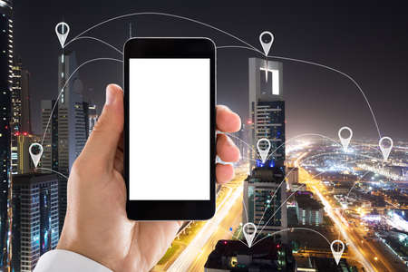Photo for Hand Holding Mobile Phone With Blank White Screen In Front Of City Showing Location Pointers - Royalty Free Image
