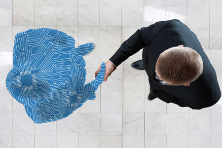 Photo pour High Angle View Of Business Man Shaking Hands With Digital Generated Human Figure - image libre de droit