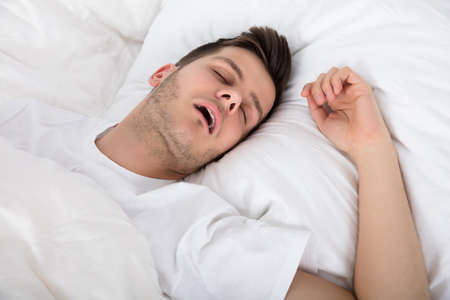 Photo pour View Of Tired Young Man Snoring While Deep Sleeping In Bed - image libre de droit