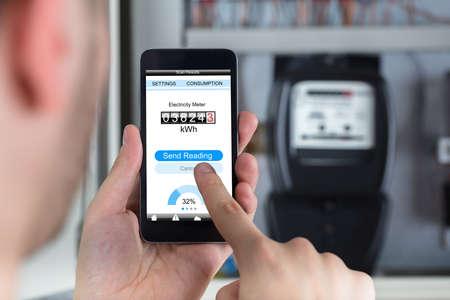 Foto de Close-up Of A Man's Hand Holding Mobile Phone Reading Electric Meter - Imagen libre de derechos