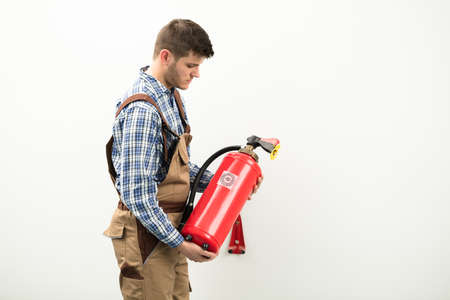 Photo pour Young Technician Carrying Red Fire Extinguisher Against White Background - image libre de droit