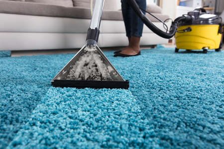 Photo pour Person Using Vacuum Cleaner For Cleaning Blue Carpet At Home - image libre de droit