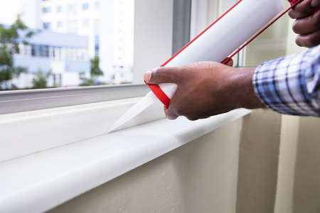 Photo for Close-up Of Person Hand Applying Silicone Sealant With Silicone Gun On Window - Royalty Free Image