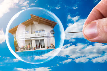 Foto de Human Hand Poking House And Bubble With Needle Against Cloudy Sky - Imagen libre de derechos