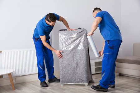 Photo for Two Young Male Movers Packing Furniture In Living Room - Royalty Free Image