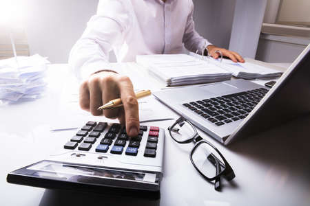 Photo pour Midsection Of Businessman Calculating Tax Using Calculator With Laptop On Desk In Office - image libre de droit