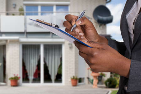 Photo pour Close-up Of A Person's Hand Filling Document In Front Of House - image libre de droit