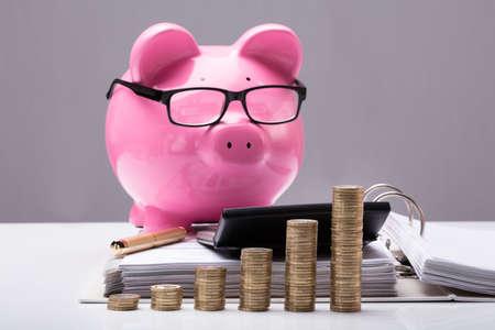 Foto de Close-up Of Stacked Coins And Document In Front Of Piggy Bank On Desk - Imagen libre de derechos