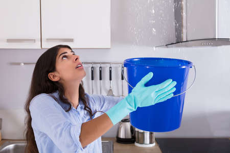 Photo pour Worried Woman Holding Bucket While Water Droplets Leak From Ceiling In Kitchen - image libre de droit