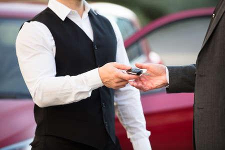 Foto de Close-up Of Valet's Hand Giving Car Key To Businessperson - Imagen libre de derechos