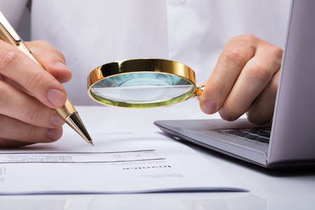 Photo for Close-up Of Auditor Inspecting Financial Documents At Desk - Royalty Free Image