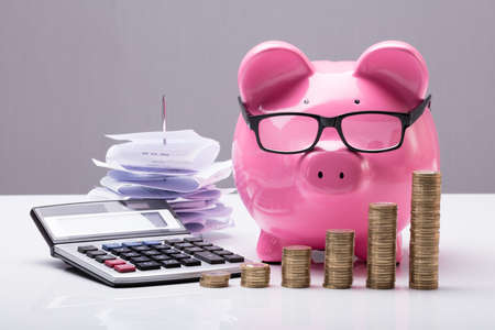 Foto de Close-up Of Stacked Coins With Piggy Bank And Calculator On Desk - Imagen libre de derechos