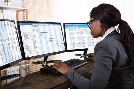 Foto de Young African Businesswoman Analyzing Gantt Chart On Computer At Workplace - Imagen libre de derechos