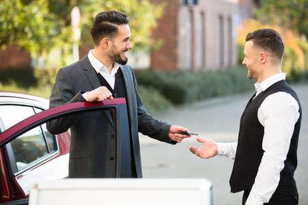 Foto de Smiling Young Businessman Standing Beside Car Giving Key To Valet - Imagen libre de derechos