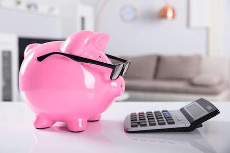 Foto de Close-up Of Pink Piggybank Wearing Spectacles With Calculator On Desk - Imagen libre de derechos