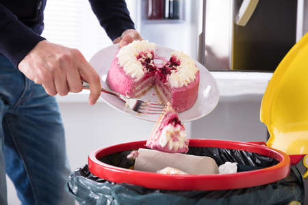 Photo for Close-up Of A Human Hand Throwing Cake In Trash Bin - Royalty Free Image