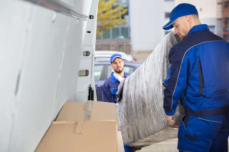 Foto per Two Happy Male Movers In Uniform Unloading Furniture From Truck - Immagine Royalty Free