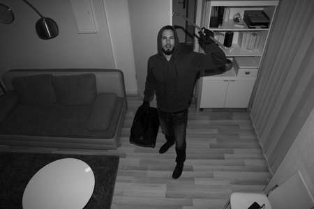 Photo for High Angle View Of A Robber Breaking CCTV Camera In Vacant House - Royalty Free Image