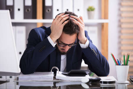 Photo pour Young Man Suffering From Headache Working In Office With Bill Over Desk - image libre de droit