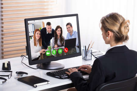 Photo pour Close-up Of A Businesswoman Video Conference With Her Colleagues On Computer In Office - image libre de droit